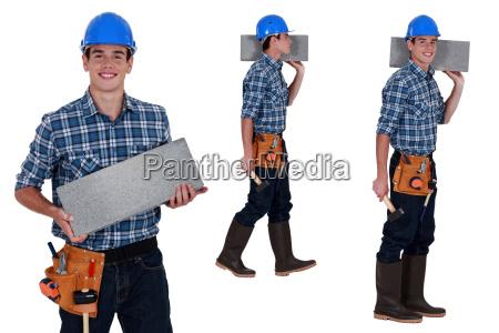 worker carrying breeze block