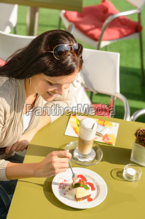 woman eating cheesecake at cafe bar