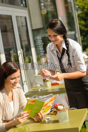 waitress taking womans order at cafe