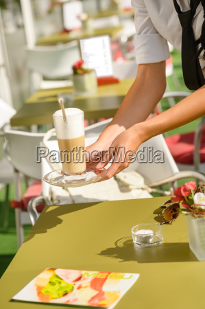 waitress hands close up serving latte