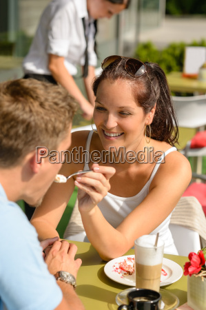 woman feeding man cheesecake at cafe