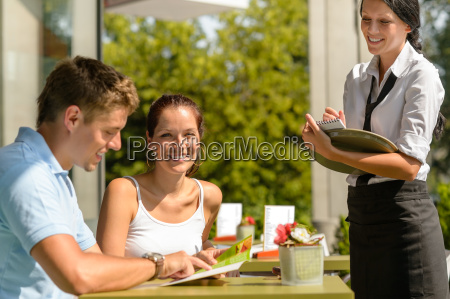 couple at cafe ordering from menu
