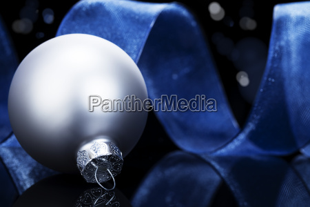 silver bauble in front of blue