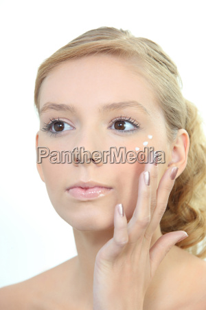 young blond woman applying beauty cream
