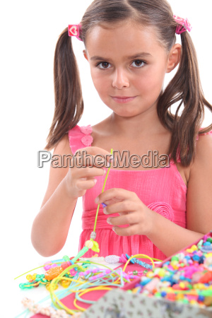 little girl making necklace