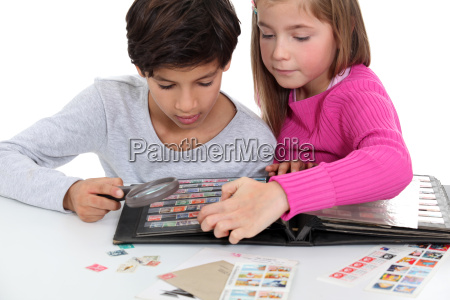 children looking at a stamp album