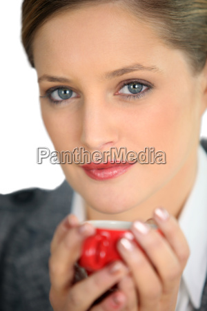 blue eyed woman drinking a cup