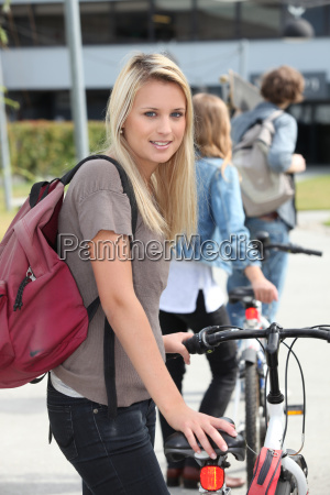 student on campus with a bike