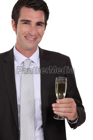 confident businessman holding glass of champagne