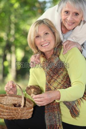 two seniors women gathering chestnuts