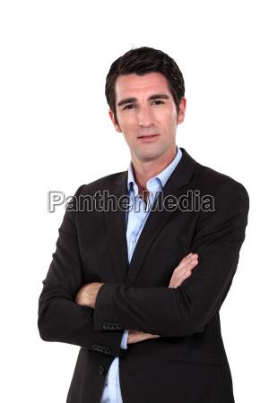 elegant man standing cross armed against