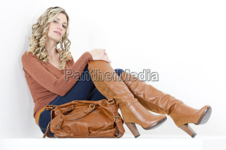 sitting woman wearing fashionable brown boots