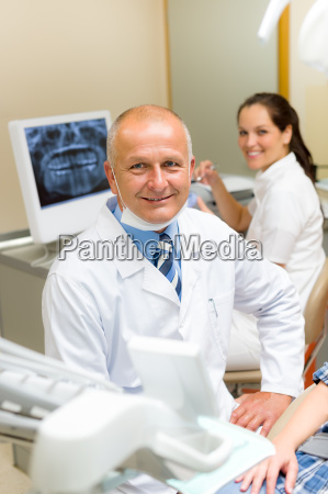 mature dental surgeon in office with