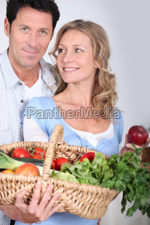 wife looking at husband with vegetable