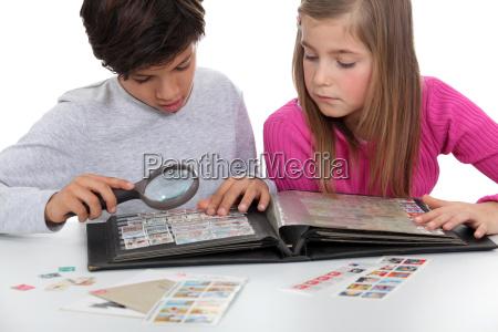 criancas assistindo um album de selos