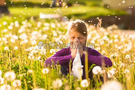girl sitting on meadow with dandelions