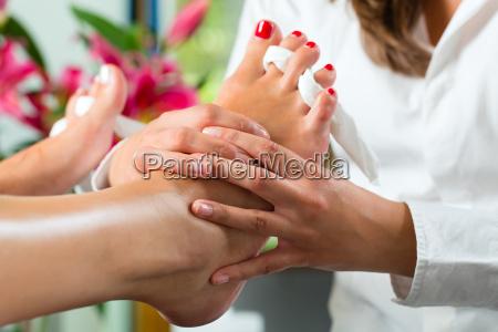 woman in beauty salon gets pedicures