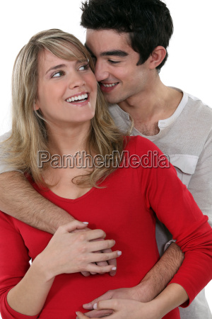 young happy couple embracing against studio