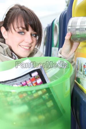 woman placing trash in recycle bin