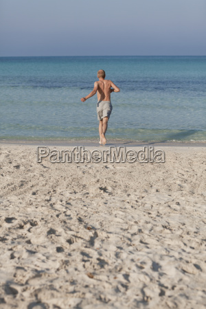 man running on the beach in