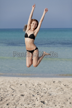 woman with bikini jumps happily on