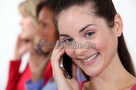 three woman using their mobiles