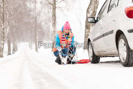 woman with tire chains car snow