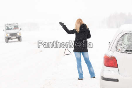 woman hitchhiking having trouble with car