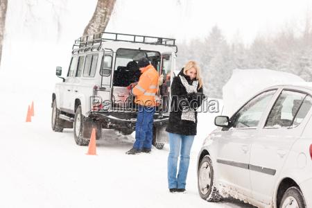 mechanic helping woman with broken car