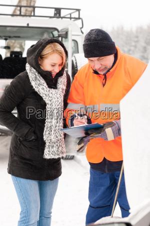 woman fill document broken car snow