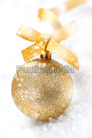 gold christmas ball in falling snow