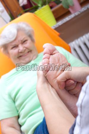 senior woman receives a foot reflexology