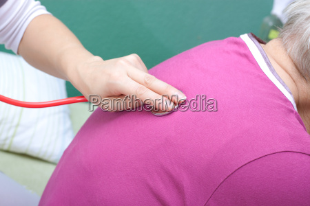 female doctor examining senior woman with