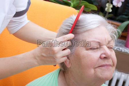 senior nurse combing through her hair