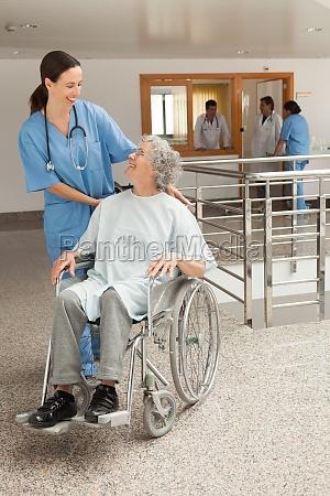 nurse smiling and kneeling beside old