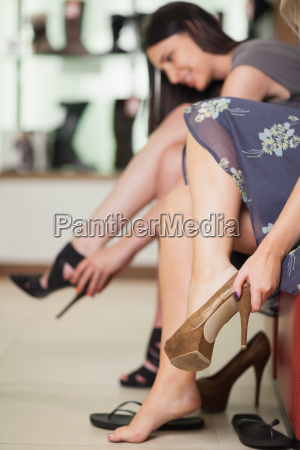 two women trying on shoes in