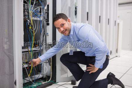 technician plugging cable into server in