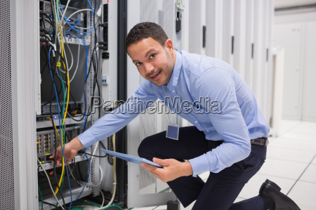 smiling technician with tablet pc plugging