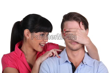 young woman covering a mans eyes