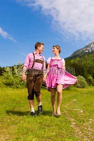 couple in tracht running on meadow