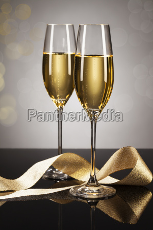 two glasses of champagne with golden