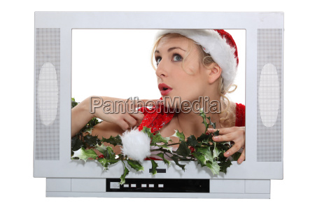 woman with christmas hat behind television