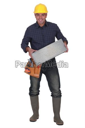 builder carrying breeze block