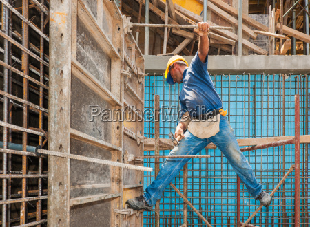 construction worker balancing between scaffold and