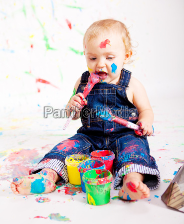 small young baby painting with colors