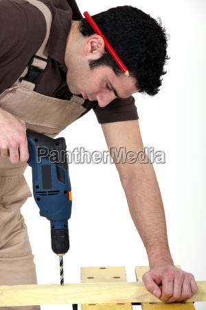craftsman making a hole with a