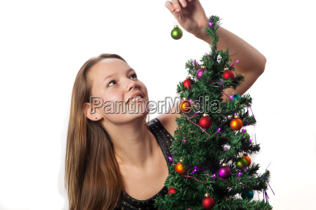 woman decorates a christmas tree