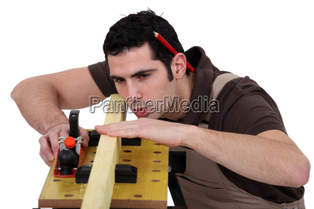 man smoothing plank of wood with