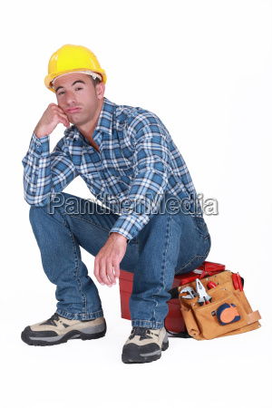 bored builder sat on tool box