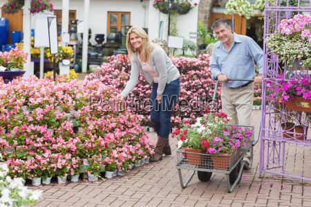 smiling couple shopping for flowers in
